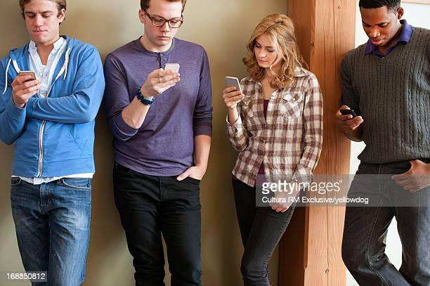 Students using cell phones in hallway