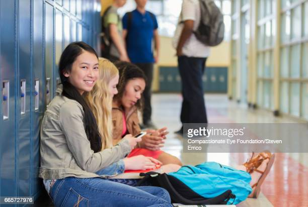 Students using cell phones in school hallway by lockers