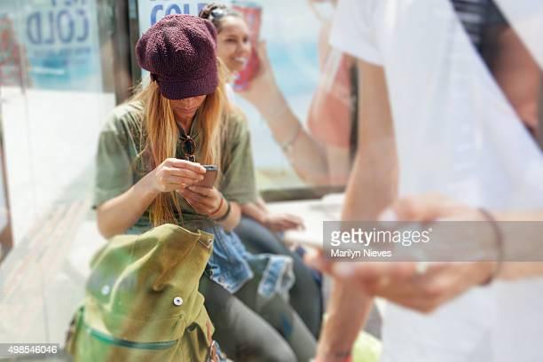 Studenten mit cellphone an der Bushaltestelle