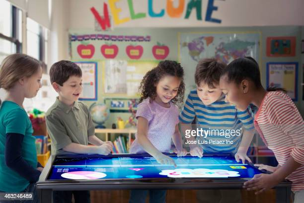 students using digital tablet in classroom - educazione primaria foto e immagini stock