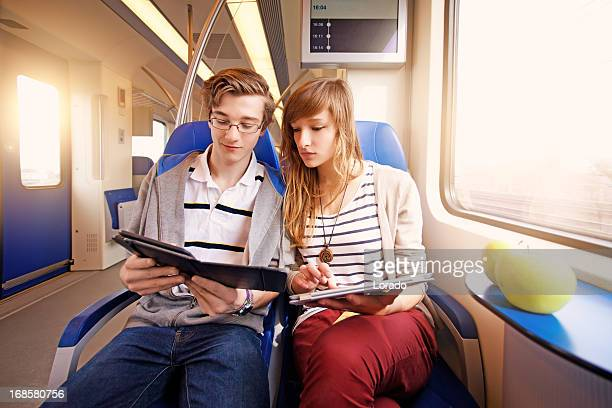 students using digital tablets in the train
