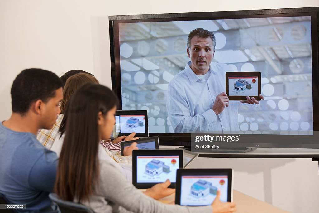 Students using digital tablets with instructor on monitor : Stock Photo