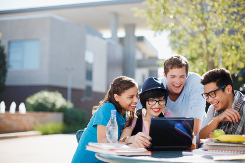 Students using laptop together outdoors - gettyimageskorea