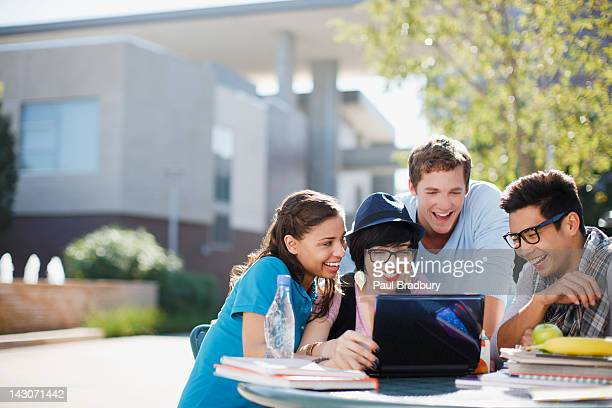students using laptop together outdoors - person in education stock pictures, royalty-free photos & images