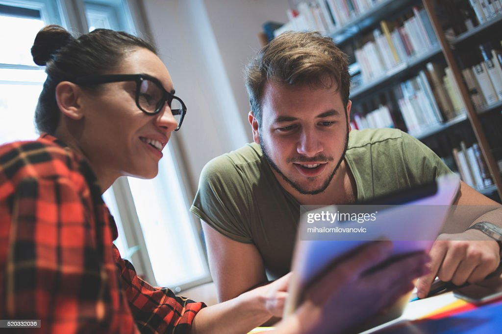 Students using tablet in library : Stock Photo