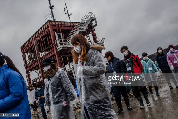 Students volunteering to help clean the Shizukawa river from Kanto region gather to their pay respects to tsunami victims at the site of the...