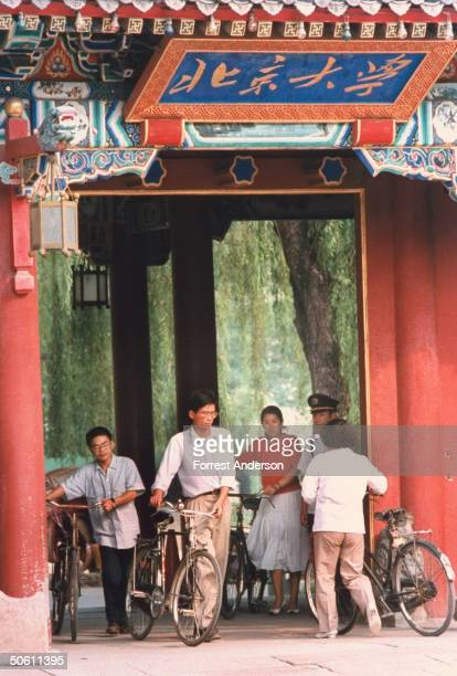 Students w bicycles walking through Qing Dynasty style gate w Peking Univ sign above re govt incentive packages to attract expatriate scholars help...