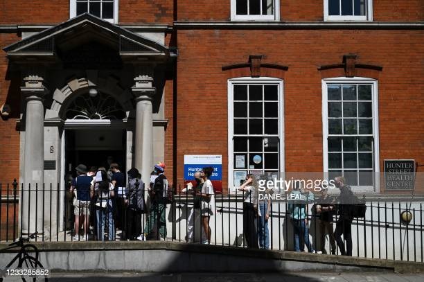 Students wait in a queue to receive a dose of the Pfizer/BioNTech Covid-19 vaccine at a vaccination centre at the Hunter Street Health Centre in...