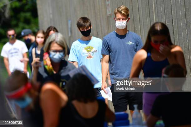 Students wait in line for registration and an identifying wristband after receiving a negative test result for coronavirus while arriving on campus...