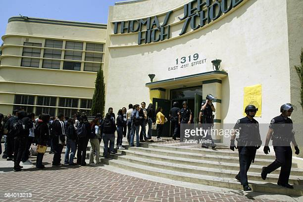 Students wait in line to be scanned by a metal detector so they can go in to get their lunches as LA School Police leave after a long morning of...
