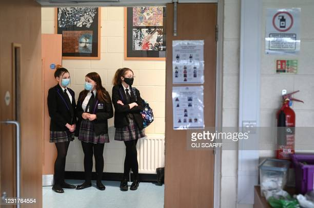 Students wait to enter a classroom at Park Lane Academy in Halifax, northwest England on March 17, 2021.