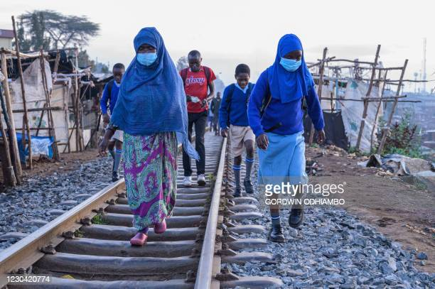Students walk along the railway to their school in the early morning of the official re-opening day of public schools on January 4 in Kibera slum,...