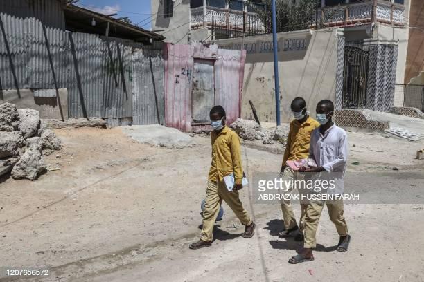 Students walk in a Mogadishu neighbourhood wearing face masks as protective measure against Coronavirus on Thursday March 19 2020 Somali prime...