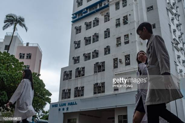 Students walk in front of University of Hong Kong's Wei Lun Hall the residential block where university professor Cheung Kiechung and his family...