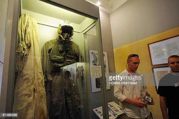 US students walk next to the flightsuit that of the current US Republican presidential candidate then US Navy Lieutnantcommander pilot John McCain...