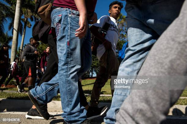 Students walk outside Marjory Stoneman Douglas High School during the ENOUGH National School Walkout rally in Parkland Florida US on Wednesday March...