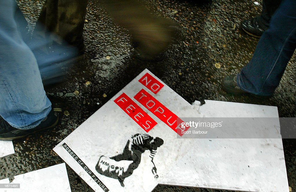 Students walk over discarded placards as they participate in a demonstration December 4, 2002 in London, England. Thousands of students marched through the streets of London to protest against student debt and any increase in fees.
