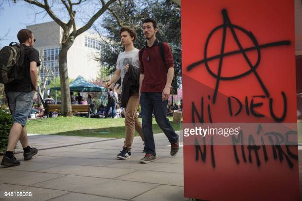 Students walk past a red flag bearing the anarchist slogan No gods no masters on the campus of the Nanterre University west of Paris on April 18 2018...