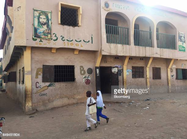 Students walk past a Shiite school run by the Islamic Movement with a poster showing Imam Hussein a figure revered by Shiites hanging on the wall in...