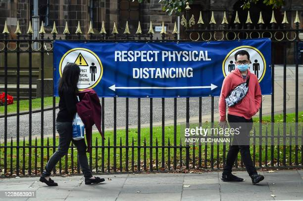 Students walk past a social distancing banner due to novel coronavirus Covid-19 in Glasgow university complex, Glasgow, Scotland on September 24,...