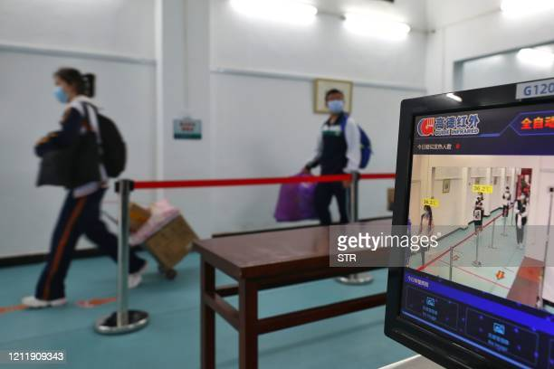 Students walk past a temperature-monitoring camera as they enter a high school in Wuhan in China's central Hubei province on May 6, 2020. - Senior...