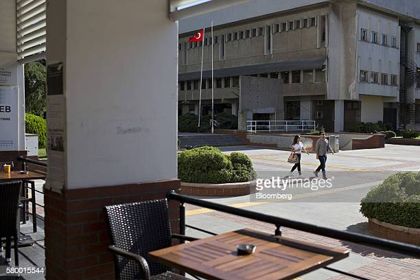Students walk past a Turkish national flag on the north campus of Bogazici university in Istanbul Turkey on Saturday July 23 2016 President Recep...
