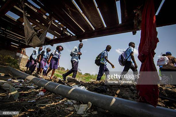 Students walk past an old bridge on September 28 2015 in Beira Mozambique
