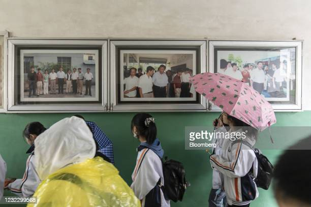 Students walk past photographs featuring Chinese President Xi Jinping during his visit to the region in 2005 inside an exhibition hall at Yucun...