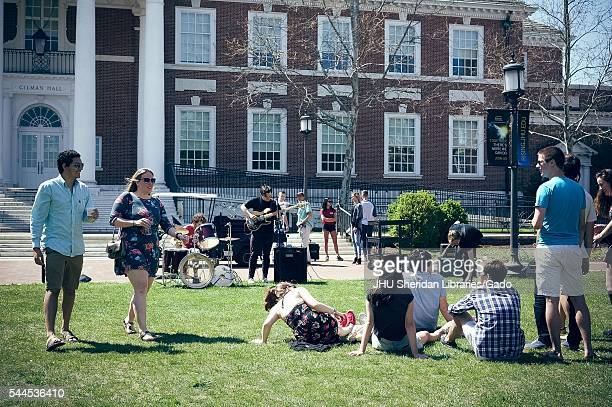 Students walk with drinks and sit on the grass to enjoy a student band playing in front of Gilman Hall during Spring Fair a studentrun spring...