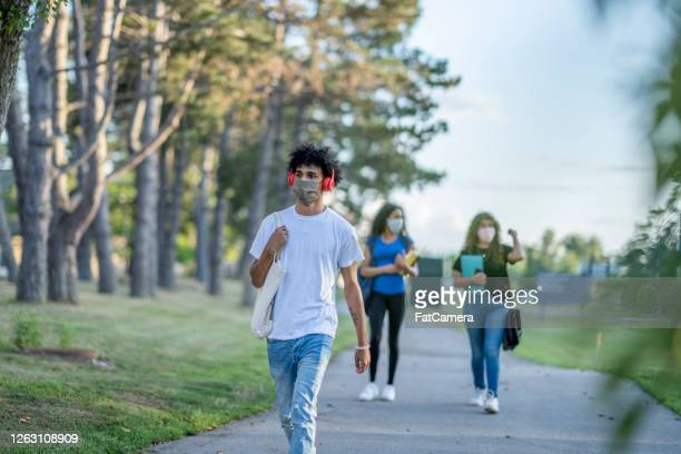 students walking on school property while wearing masks - fatcamera stock pictures, royalty-free photos & images
