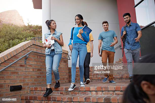 students walking out of school building - community college stock pictures, royalty-free photos & images