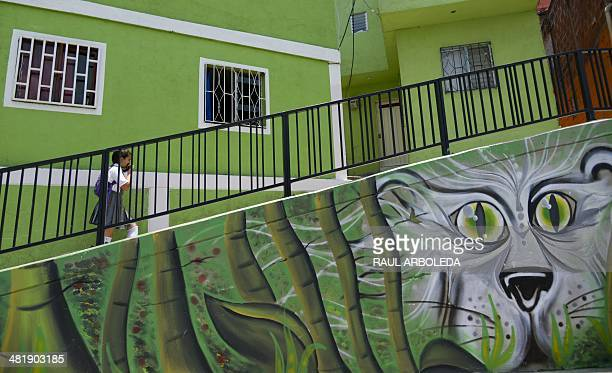 A students walks past a mural part of the project Medellin is painted for life at Comuna 13 shantytown one of the poorest areas of Medellin Antioquia...