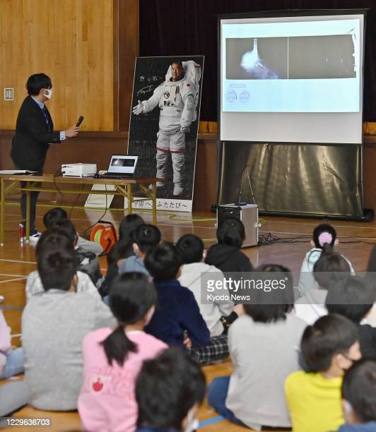 Students watch a live broadcast of the launch of the SpaceX ship carrying Japanese astronaut Soichi Noguchi on a screen on Nov. 16 at Noguchi's old...
