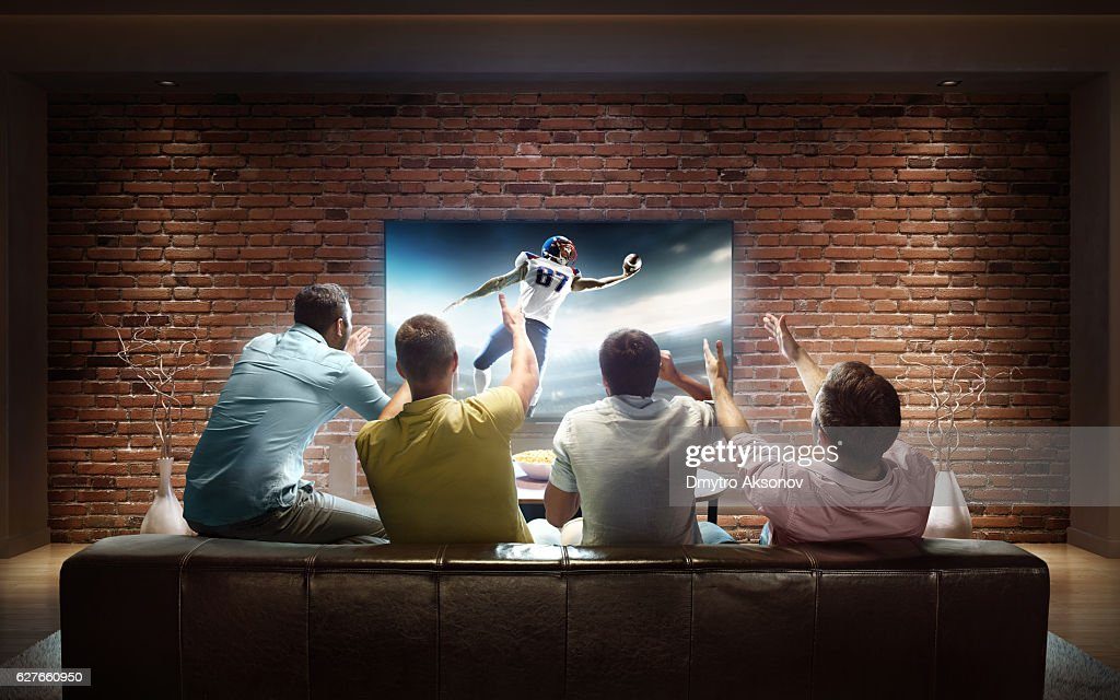 Students watching American football game at home : Stock Photo