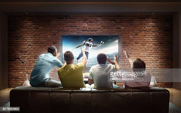 students watching american football game at home - football stock pictures, royalty-free photos & images