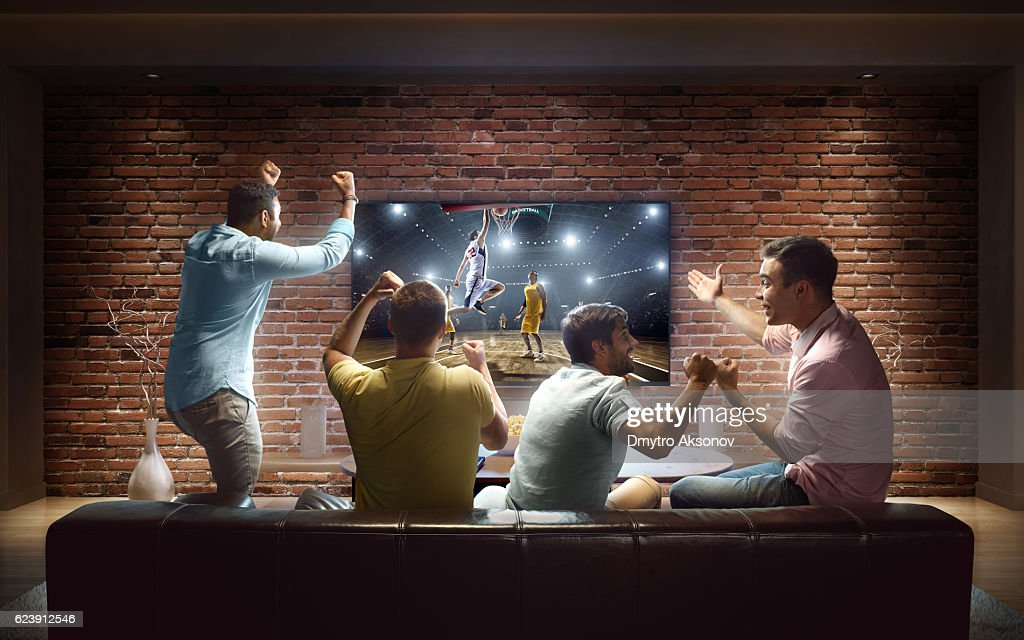 Students watching Basketball game at home : Stock Photo