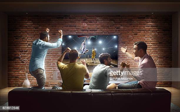 students watching basketball game at home - guardare con attenzione foto e immagini stock
