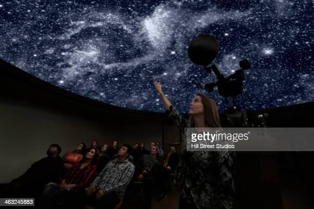 Students watching galaxy in planetarium