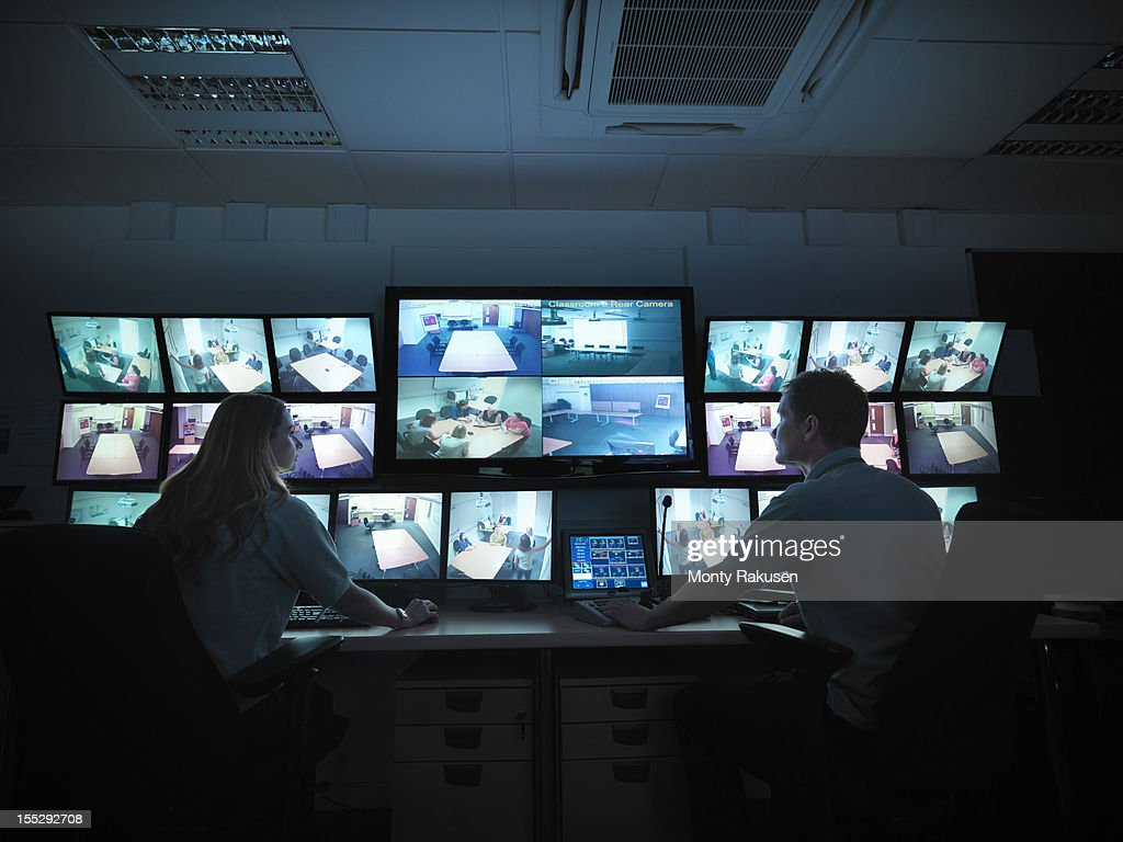 Students watching screens in forensics training facility : Stock Photo