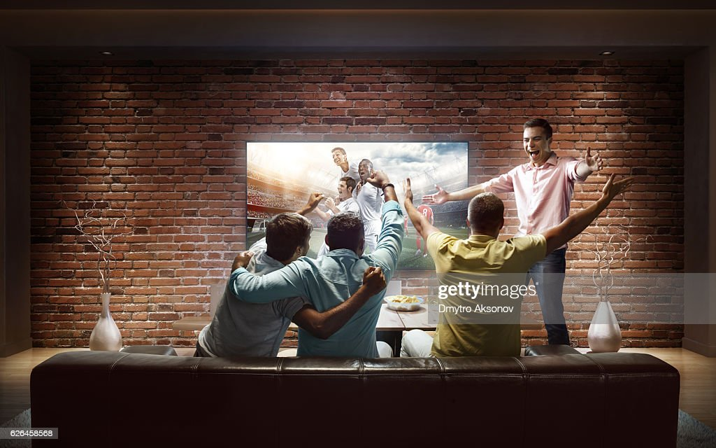 Students watching Soccer game at home : Stock Photo