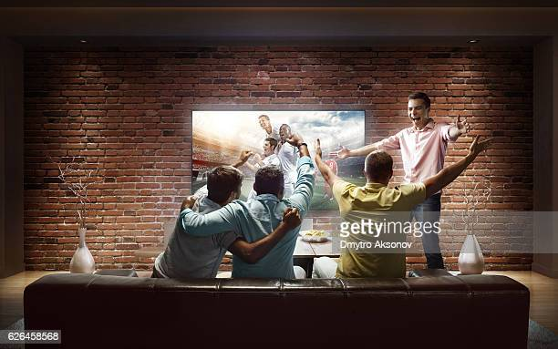 students watching soccer game at home - match sport imagens e fotografias de stock