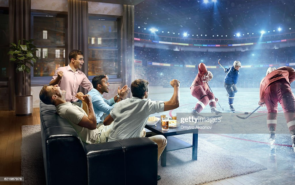 Students watching very realistic Ice hockey game at home : Stock Photo