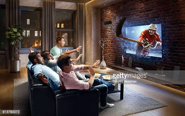 students watching very realistic ice hockey game on tv - puck stock pictures, royalty-free photos & images