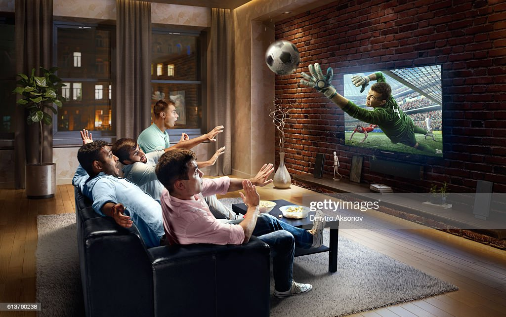 Students watching very realistic Soccer game on TV : Stock Photo
