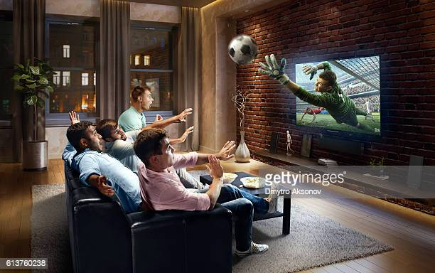 students watching very realistic soccer game on tv - mirar un objeto fotografías e imágenes de stock