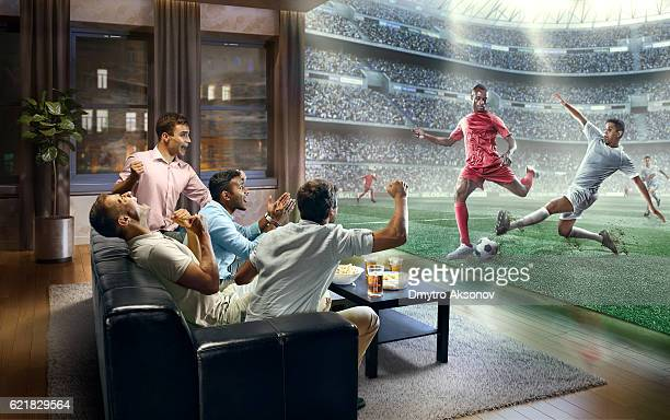 students watching very realistic soccer game on tv - fußball stock-fotos und bilder