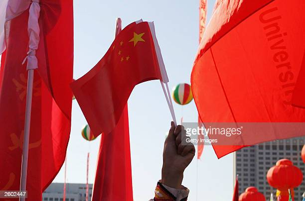 Students wave national flags to celebrate China's first manned spaceship on October 16, 2003 in Beijing, China. China launched its first manned...