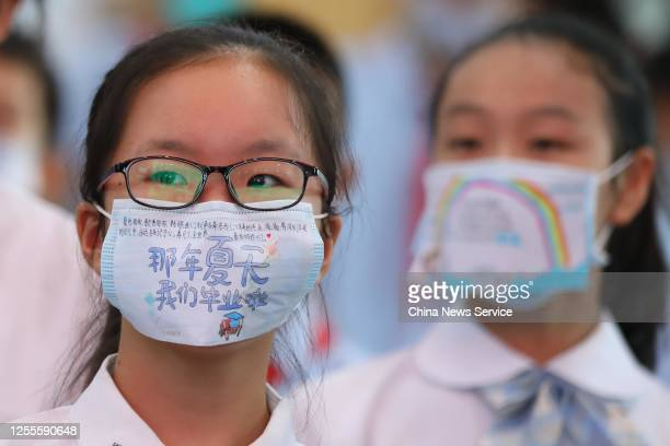 Students wear face masks with blessing messages during a graduation ceremony at a primary school on July 11 2020 in Nanjing Jiangsu Province of China