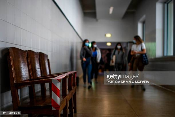 Students wearing a face mask arrive to enter a classroom on the first day of school after the relief of emergency measures due to the COVID19...