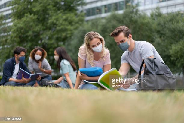 students wearing a facemask while studying outdoors - state of emergency stock pictures, royalty-free photos & images